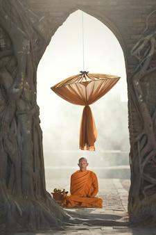 Monge budista durante o nascer do sol no templo, tailândia