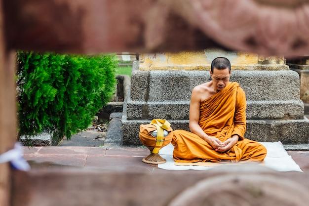 Monge budista indiano em meditação perto da árvore de bodhi perto do templo de mahabodhi