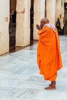 Monge budista indiano em pé e rezando em pé descalço no templo de mahabodhi