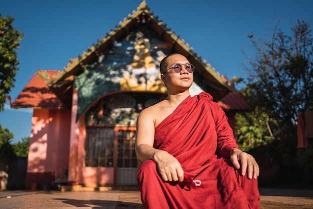 Monge budista sentado em frente a um pequeno templo ao pôr do sol. templo budista em misiones, argentina.