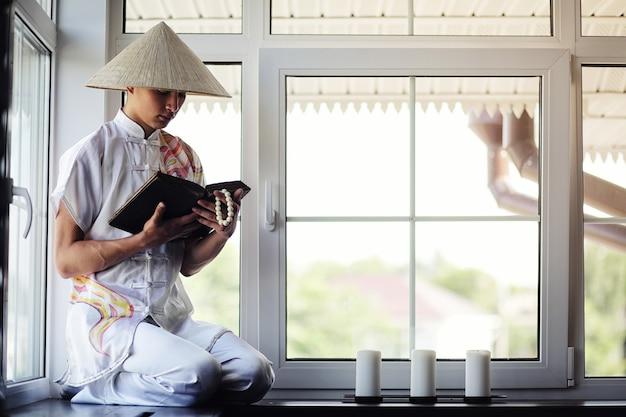 Monge menino asiático de quimono lendo um livro antigo