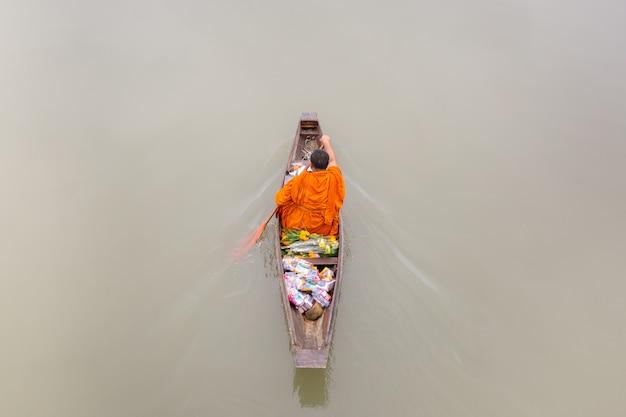 Monge no barco das fileiras que recebe ofertas do alimento das pessoas ao longo do canal.