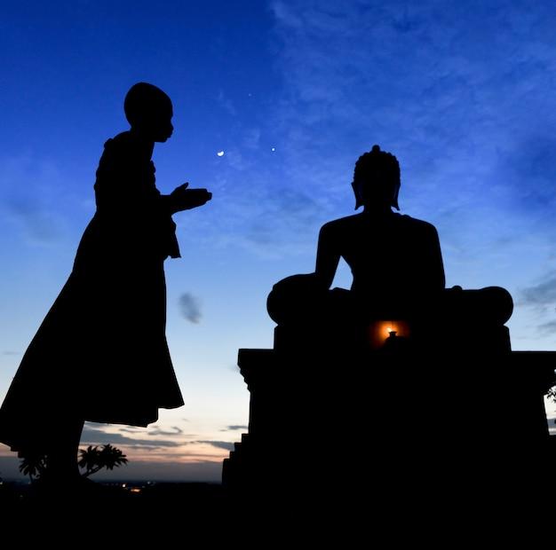 Monge noviço rezando para a estátua do buda