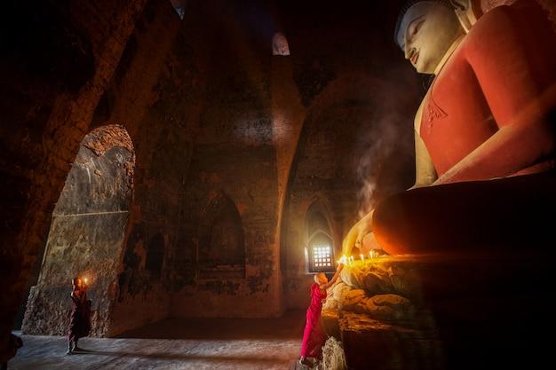 Monge rezando para uma estátua de buda com uma vela