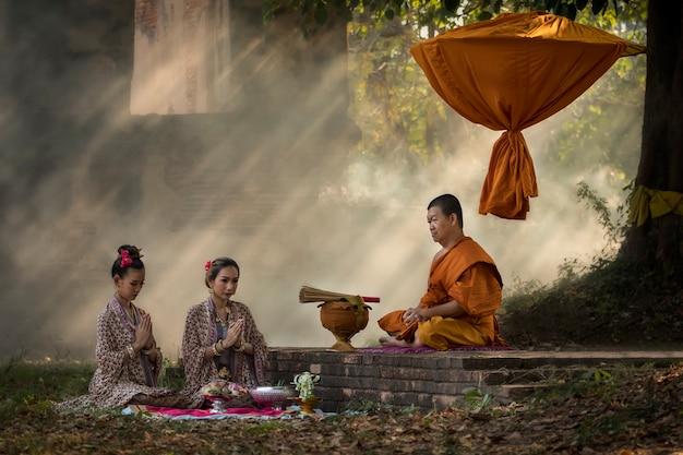 Monges asiáticas que meditam a árvore na iluminação do templo.