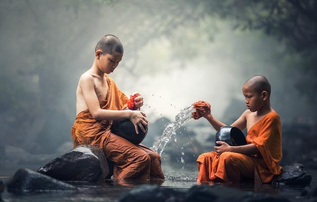 Monges asiáticos noviço limpeza tigela de esmolas em riachos
