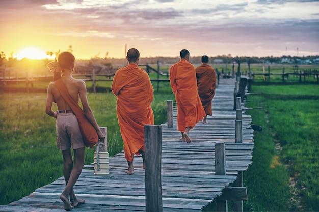 Monges budistas na esmola tradicional da manhã todos os dias dando na tailândia.