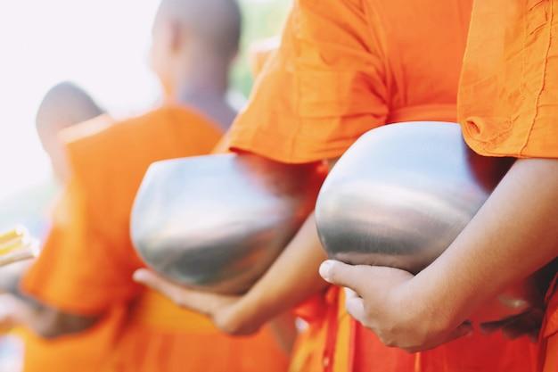 Monges com a mão segurando dar esmola tigela no templo budista, cultura e religião.