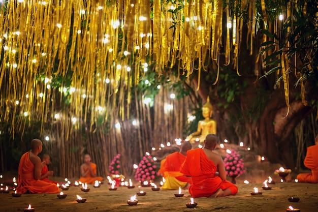 Monges sentados meditando com muitas velas no templo tailandês à noite