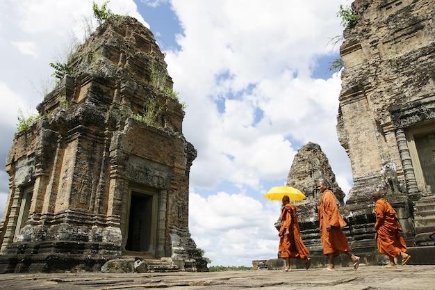 Monges tibetanos em vestes alaranjadas que visitam templos cambojanos remotos meditar.