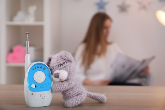 Monitor de bebê, brinquedo e mulher diante. babá de rádio