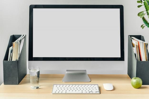Monitor de computador com tela branca de maquete na mesa de escritório com suprimentos