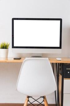 Monitor de computador com tela branca em branco na mesa de trabalho com mouse sem fio, teclado