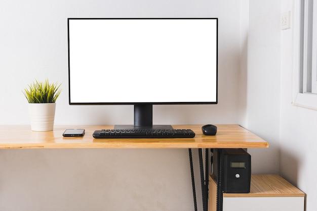 Monitor de computador com tela branca em branco na mesa de trabalho