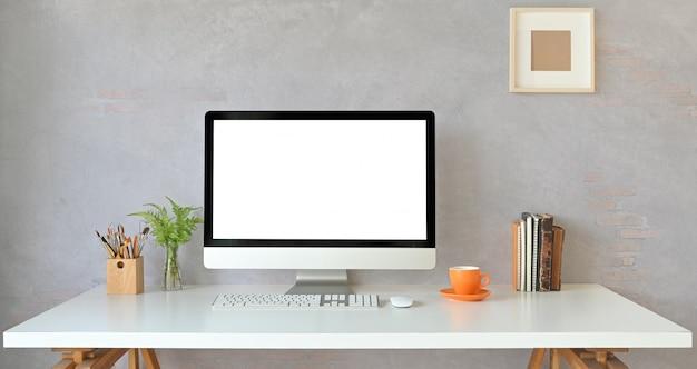 Monitor de computador de espaço de trabalho com tela branca em branco, colocando na mesa de trabalho branca com livros, xícara de café, vaso de plantas, porta-lápis, mouse e teclado sem fio. conceito de local de trabalho em ordem.