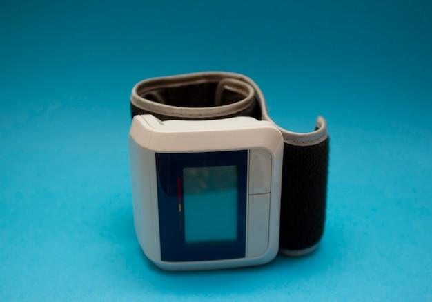 Monitor de pressão arterial digital automático de pulso sobre fundo azul.