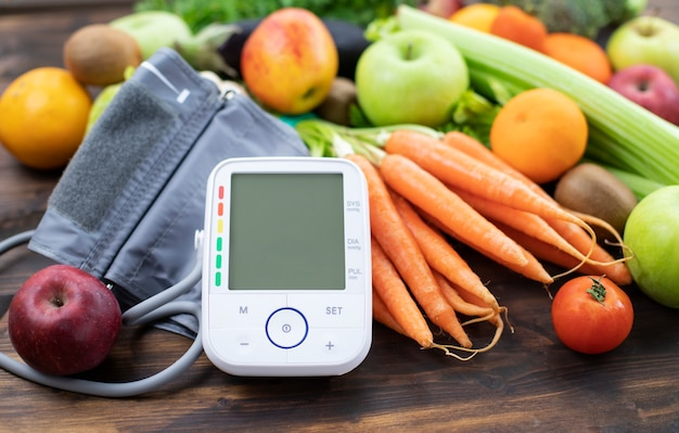 Monitor de pressão arterial e frutas frescas com vegetais contra a mesa de madeira estilo de vida saudável e conceito de prevenção da hipertensão