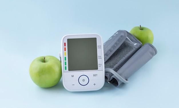 Monitor de pressão arterial e maçãs verdes frescas. estilo de vida saudável e conceito de prevenção da hipertensão