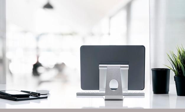 Monitor de tablet de retrovisor no suporte de suporte e suprimentos na mesa branca com fundo desfocado.