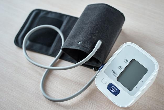 Monitor digital da pressão sanguínea na tabela, close up. helathcare e conceito médico