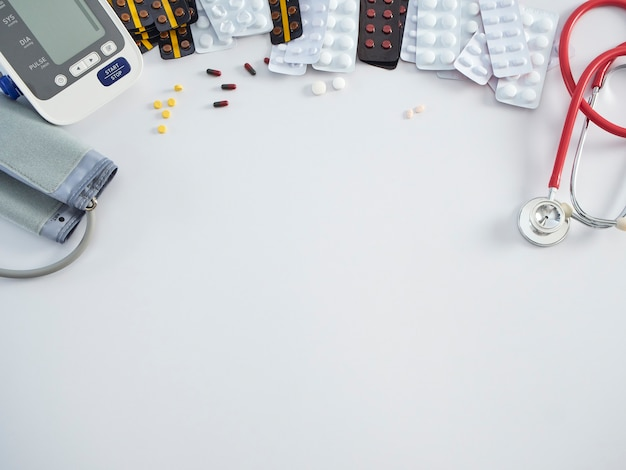 Monitor digital de pressão arterial com estetoscópio médico e medicamentos em fundo branco. conceito de saúde e medicina