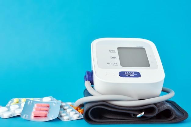 Monitor digital de pressão arterial e comprimidos médicos. conceito de cuidados de saúde e medicina