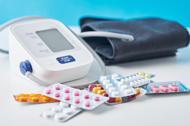 Monitor digital de pressão arterial e comprimidos médicos na mesa branca. conceito de cuidados de saúde e medicina