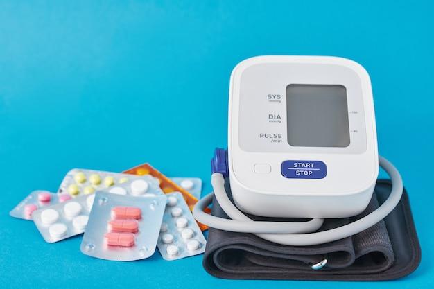 Monitor digital de pressão arterial e comprimidos médicos sobre fundo azul. conceito de cuidados de saúde e medicina