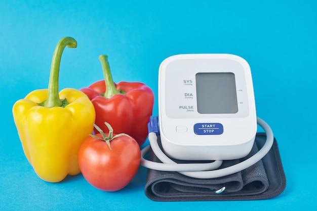Monitor digital de pressão arterial e legumes frescos na superfície azul