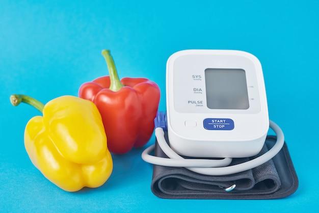 Monitor digital de pressão arterial e legumes frescos pimenta no azul