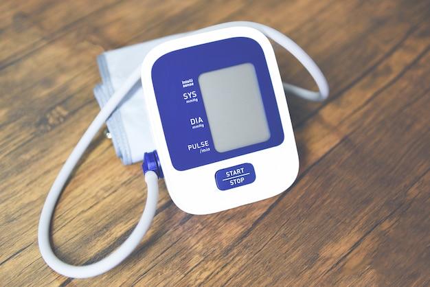 Monitor digital de pressão arterial na mesa de madeira, tonômetro eletrônico médico para verificar a pressão arterial
