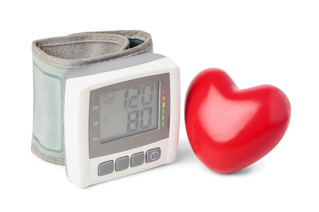 Monitor digital de pressão arterial (tonômetro) com coração vermelho decorativo perto, isolado no fundo branco.