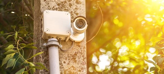 Monitoramento cctv externo, banner, câmeras de segurança com reflexo de luz solar ao pôr do sol