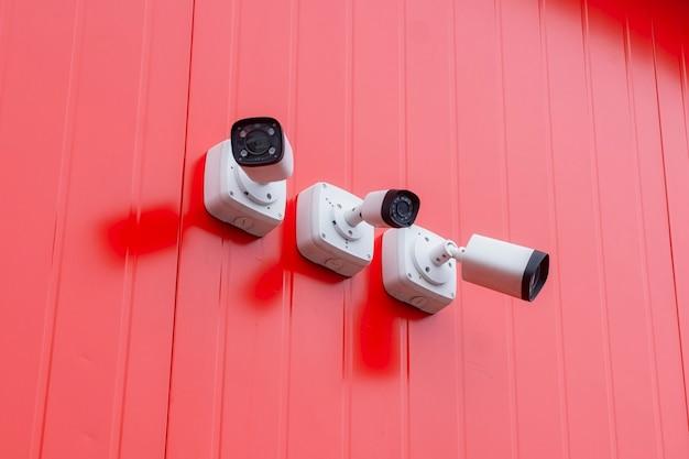 Monitoramento de cftv. câmera de vigilância de vídeo externa para proteção de objetos no prédio vermelho.