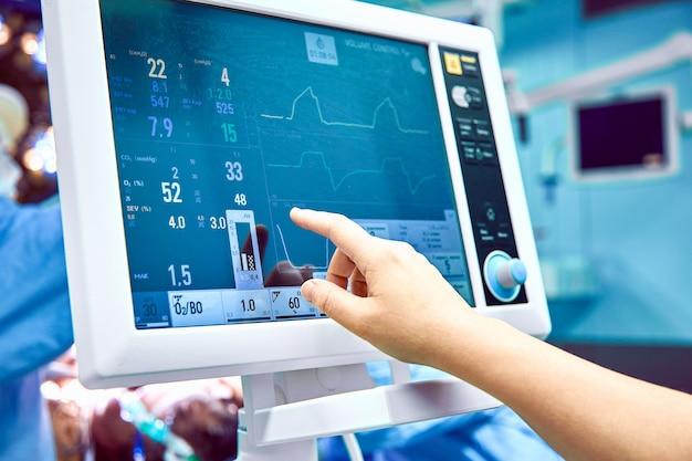 Monitorando o sinal vital do paciente na sala de cirurgia. médico mastigando os sinais vitais do paciente. monitor de eletrocardiograma durante a cirurgia na sala de operação.