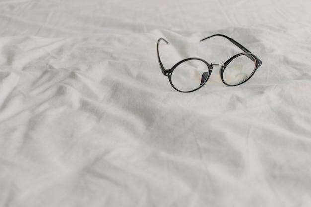 Monóculos com o templo plástico preto na folha de cama branca.