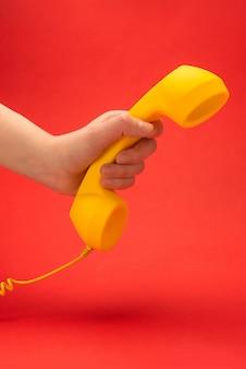 Monofone amarelo em um vermelho na mão da mulher.