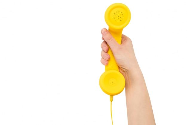 Monofone amarelo na mão da mulher isolada no branco.