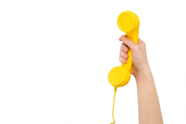 Monofone amarelo na mão da mulher isolada