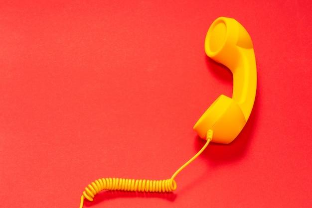 Monofone amarelo na superfície vermelha. copie o espaço.