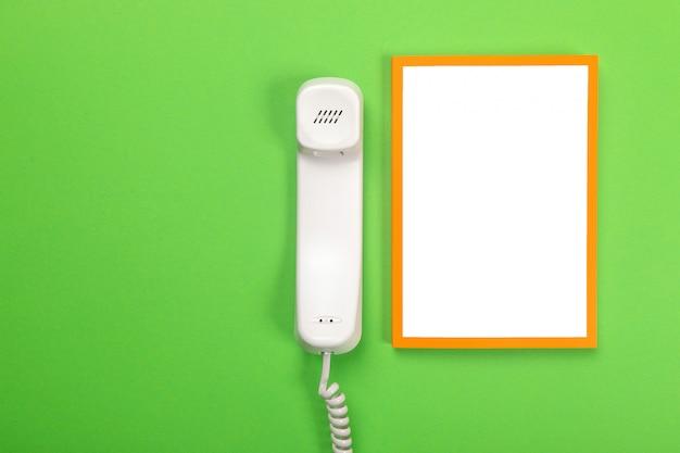 Monofone do telefone e a folha branca mentem isolado em verde