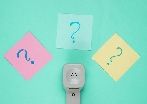 Monofone retrô e pontos de interrogação em pedaços de papel de memorando