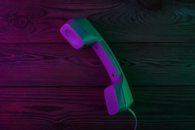 Monofone retrô em superfície de madeira com luz de néon verde e magenta