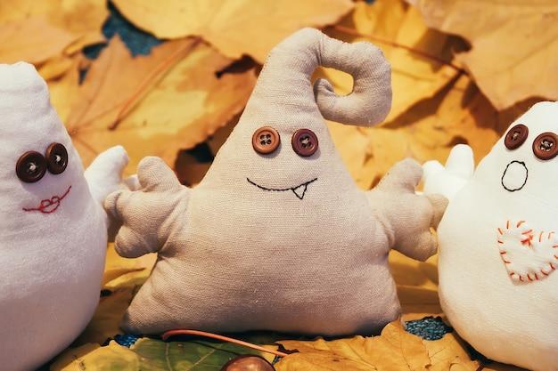 Monstros de brinquedo com olhos de botão entre as folhas