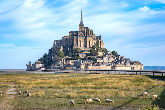 Mont saint michel e a abadia com o mar na maré baixa e obedecem a pastagem