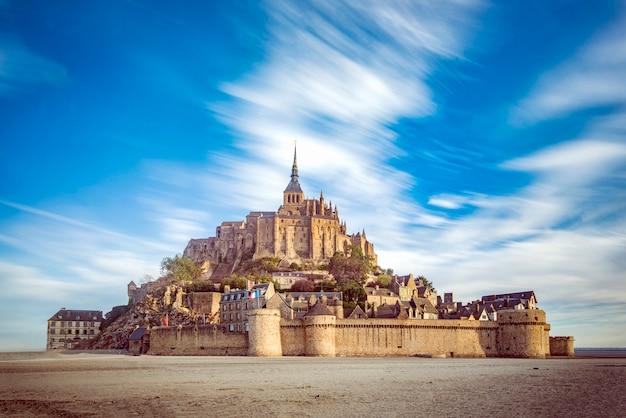 Mont saint michel e sua abadia com o mar na maré baixa e nuvens se movendo pelo vento forte