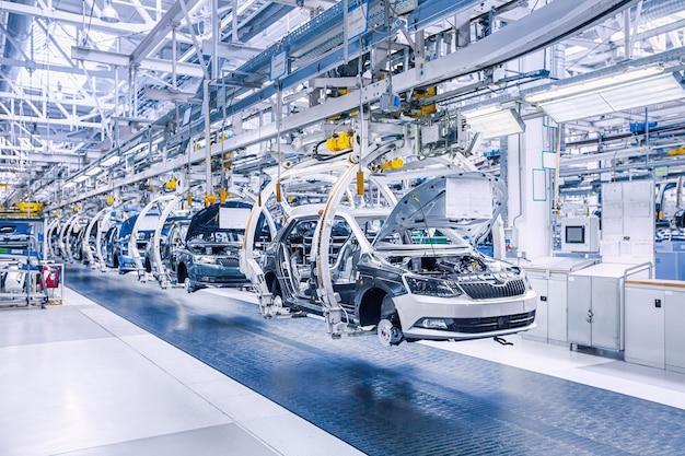 Montagem de carros na linha de transporte na fábrica de carros