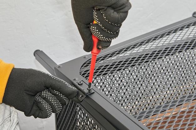 Montagem de dobradiças de porta em móveis de aço, faz-tudo aperta o parafuso.
