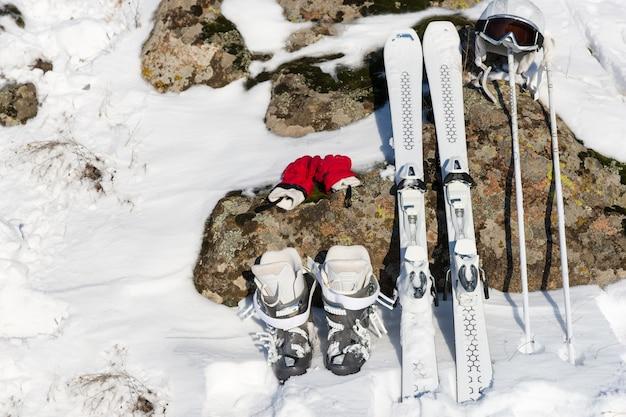 Montagem de esportes de inverno com luvas vermelhas, par de esquis, botas, capacete e bastões apoiados em superfície de pedra parcialmente coberta de neve