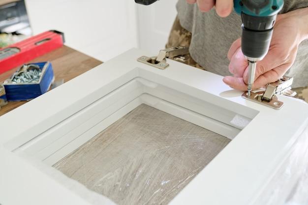 Montagem de móveis, close-up aparafusando dobradiças cromadas com ferramentas profissionais